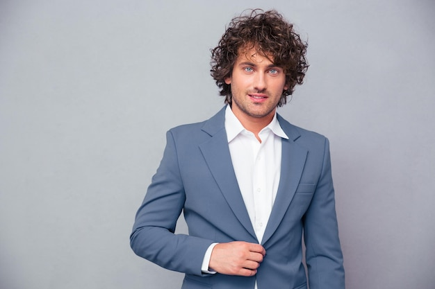 Portrait of a happy businessman with curly hair looking at front over gray wall