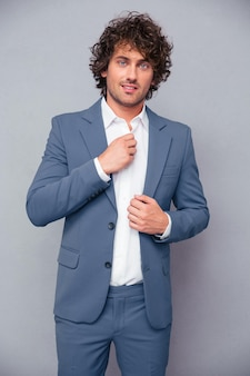 Portrait of a happy businessman with curly hair standing over gray wall