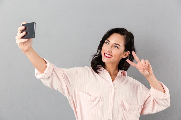 Portrait of a happy businesswoman taking a selfie