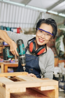 Portrait of happy carpenter in protective glasses using drill when making wooden furniture in workshop