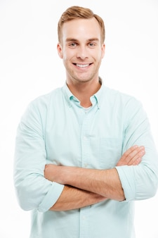 Portrait of a happy casual man standing with arms folded over white wall and looking at front