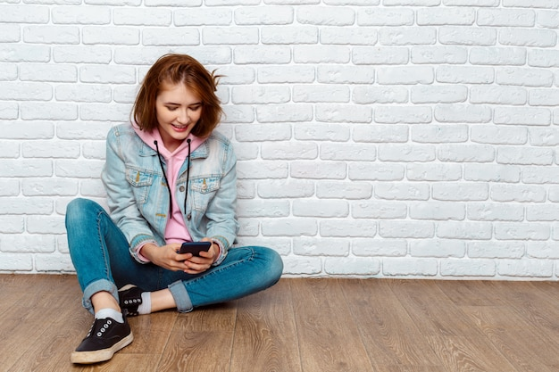 Portrait of a happy casual woman sitting on the floor and using smartphone