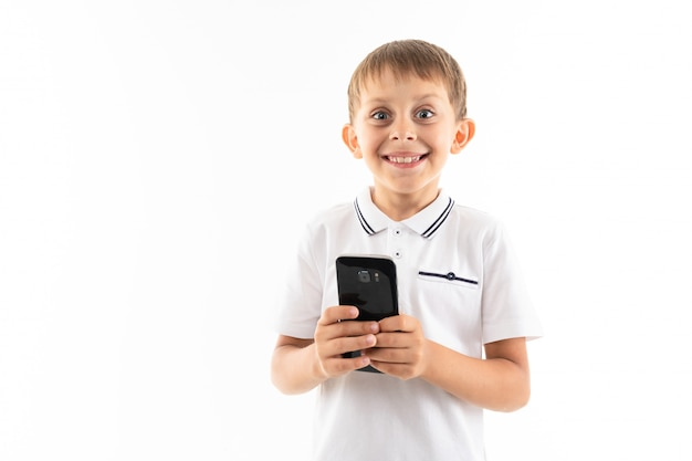 Portrait of happy caucasian boy chatting with his friends or playing phone games, wins and smiles