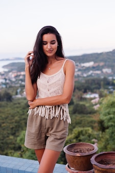 Portrait of happy caucasian calm romantic woman in casual look with long hair wearing earings and necklace on background amazing beautiful view on green mountains