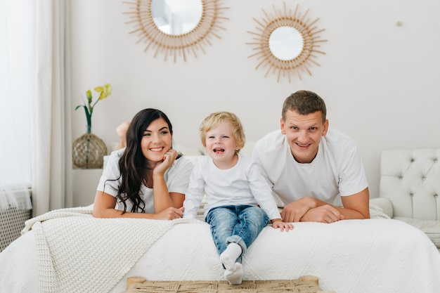 Portrait of a happy caucasian family lying on bed and smacking while looking at camera at home