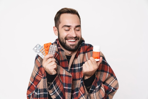 Portrait of happy caucasian guy wrapped in blanket holding bunch of tablets due to flu isolated over white wall