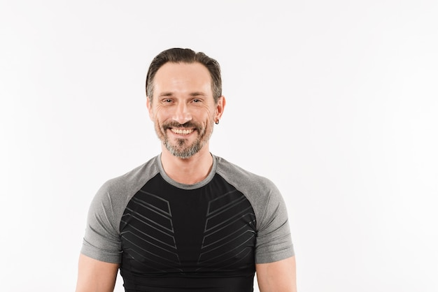 Portrait of happy caucasian man 30s wearing sportswear posing on camera with smile and satisfied look after fitness or practising