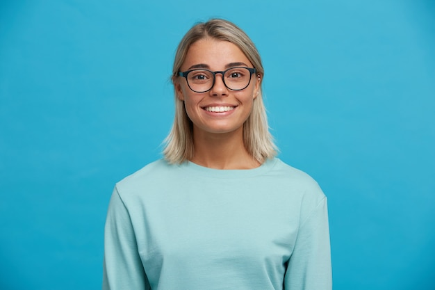 Portrait of happy charming cheerful blonde young woman in glasses, smiles