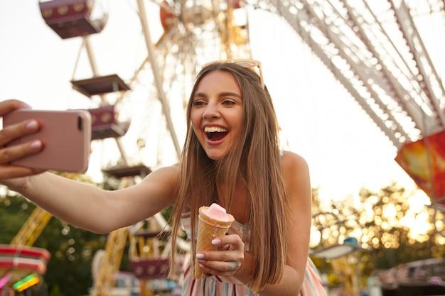 Ritratto di felice affascinante giovane donna bruna che indossa abiti estivi leggeri, facendo selfie all'aperto con il suo smartphone, tenendo il cono gelato in mano e sorridendo con gioia