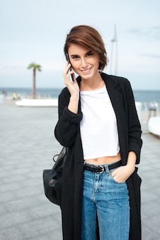 Portrait of happy charming young woman talking on mobile phone outdoors