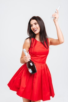 Portrait of happy charming young woman with glass and bottle of champagne over white background