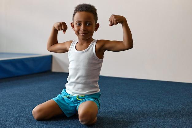 Ritratto di felice allegro ragazzo dalla pelle scura con breve acconciatura afro che si esercita al centro fitness