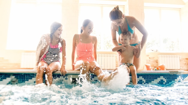 Portrait of happy cheerful family sitting on the poolside and splashing water with feet. family playing and having fun at swimming pool