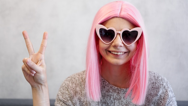 Portrait of a happy cheerful girl showing peace gesture. woman wearing heart-shaped glasses and pink wig - positive portrait
