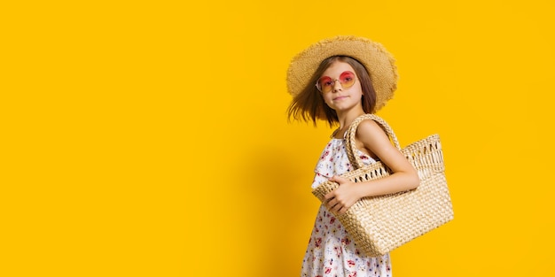 Portrait of happy cheerful girl in summer hat sunglasses straw bag over yellow background