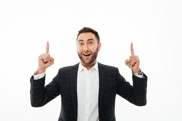 Portrait of a happy cheerful man pointing two fingers up
