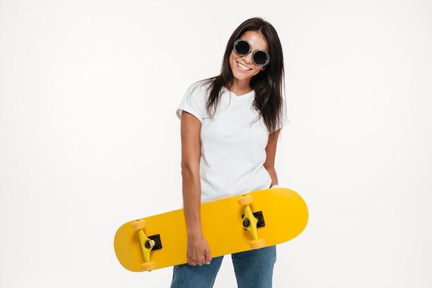 Ritratto di una donna allegra felice che tiene skateboard
