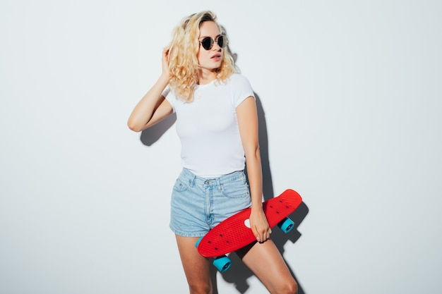 Portrait of a happy cheerful woman in sunglasses posing with skateboard while standing over white wall
