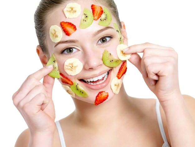 Portrait of happy cheerful young beautiful woman with fruit facial mask - isolated on white