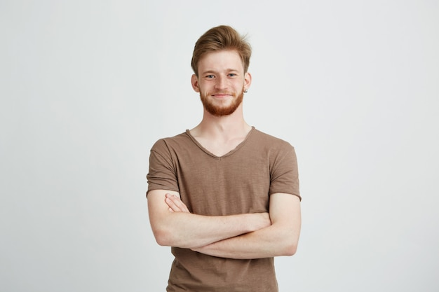 Portrait of happy cheerful young man with beard smiling with crossed arms.