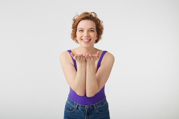 Ritratto di felice allegra giovane bella signora dai capelli corti, ampiamente sorridente, mostra qualcosa nei suoi palmi, si leva in piedi sopra il muro bianco.