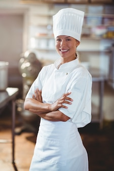 Portrait of happy chef standing with arms crossed