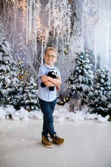 Portrait of happy child boy with big glasses holding toy bear indoor studio