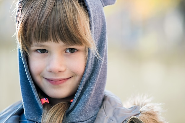 Portrait of happy child girl in warm clothes in autumn outdoors.
