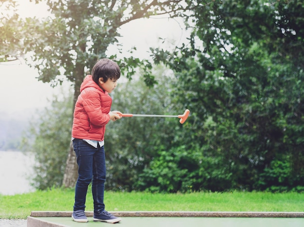 Portrait of happy child playing mini golf in the park, active kid boy playing golf on holiday, children enjoying his vacation outdoors activity