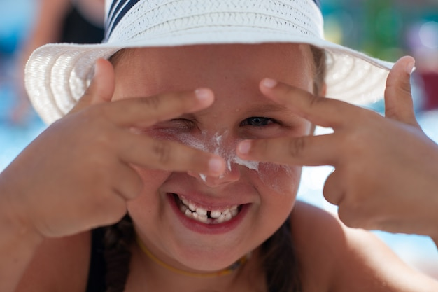 Portrait of happy child. smiling little girl in white panama hat makes faces and enjoys her summer vacation at water park.