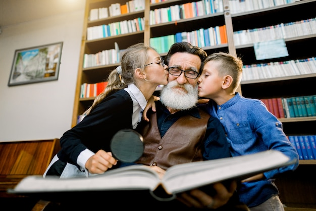 Portrait of happy children, boy and girl, kissing their old bearded granddad in cheeks while spending time, reading amazing book together in the library or cozy room at home