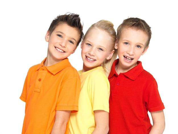 Ritratto dei bambini felici isolati su bianco. amici dello scolaro che stanno insieme e che esaminano macchina fotografica