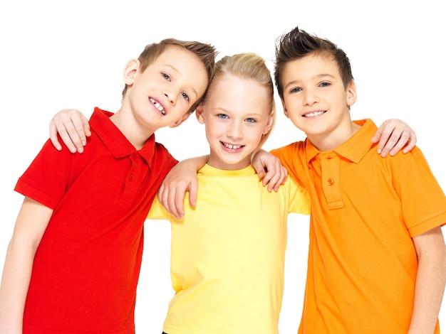 Ritratto dei bambini felici isolati su bianco. amici dello scolaro che stanno insieme e