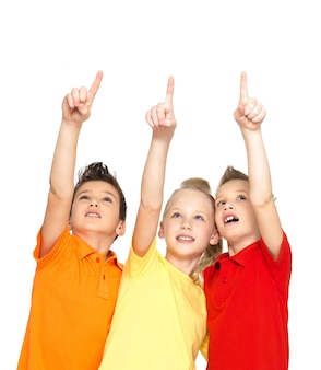 Portrait of the happy children point up by fingers on something away -  isolated on white