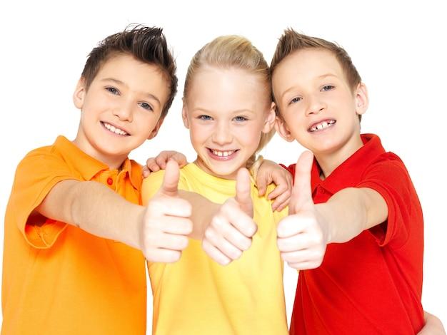 Il ritratto dei bambini felici con i pollici aumenta il gesto isolato su bianco.