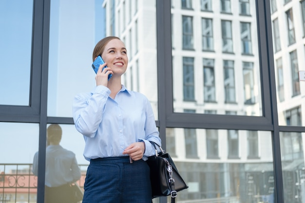 Portrait of happy confident young business woman talking on phone while stand in city outdoor. millennials life. high quality photo