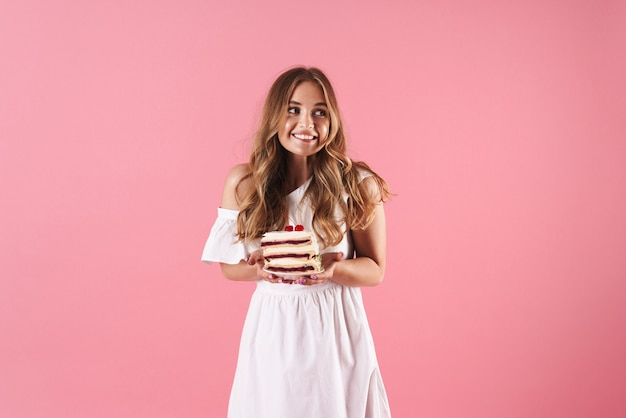 Portrait of happy confused woman wearing white dress looking aside and holding piece of cake isolated over pink wall