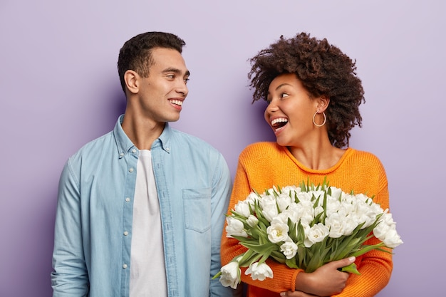 Portrait of happy couple and bouquet of flowers
