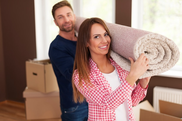 Portrait of happy couple carrying carpet for new home