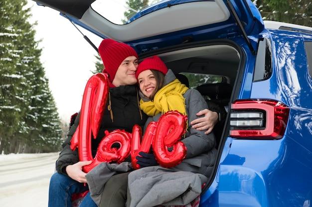 Портрет счастливой пары лиц. красные шары в форме сердца и слово любовь. празднование дня святого валентина