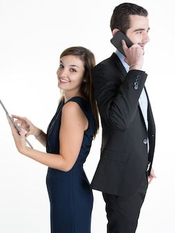 Portrait of a happy couple girl and  guy standing back to back both using smartphone and a tablet and smiling, isolated on grey hanukkah decoration