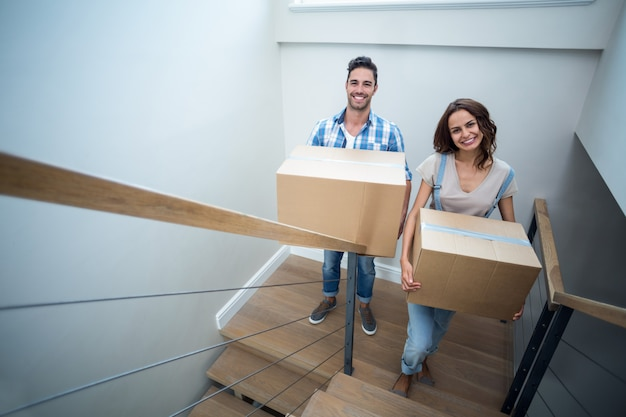 Portrait of happy couple holding cardboard boxes