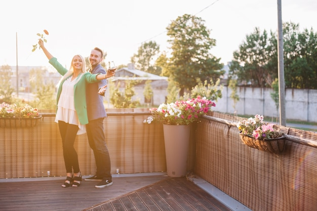 Portrait of happy couple holding wineglass and rose posing in balcony