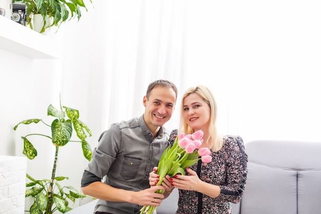 Portrait of happy couple, husband and wife with spring flower bouquet