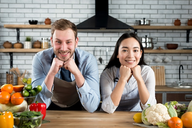 Portrait of happy couple looking at camera in their modern kitchen wearing apron