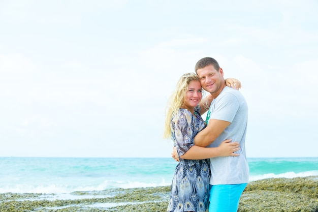 Portrait of a happy couple in love on the beach at summer day
