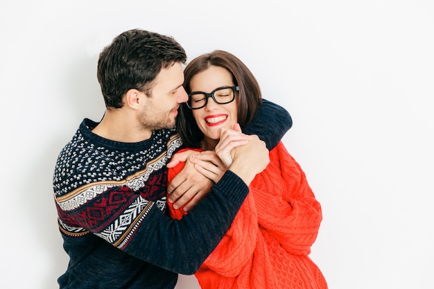 Portrait of happy couple in love embrace each other, have positive smiles