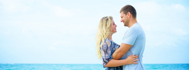 Portrait of a happy couple in love hugging on the beach at summer day