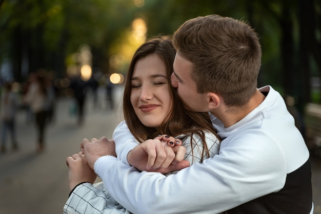 Portrait of happy couple in love in park. guy hugs his beloved by shoulders and kiss.