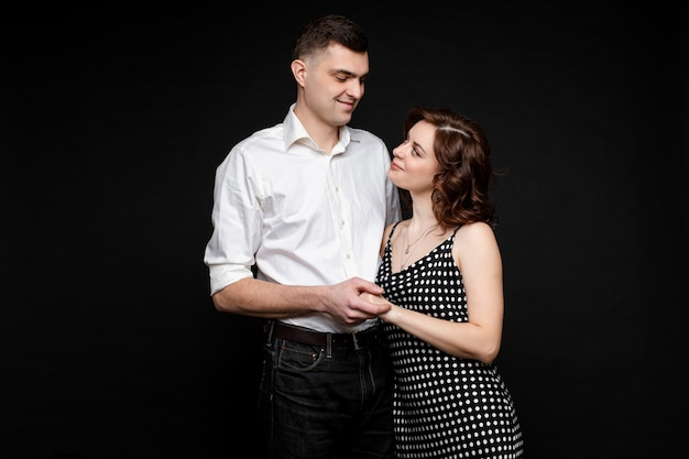 Portrait of happy couple in love stands and hugs together, picture isolated on black wall